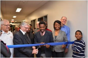 Brother F. Louis-Paul Lavallée, FSC, Visitor of the Francophone Canada district, cuts the ribbon with the help of Mr. Frantz Benjamin, city councilor of the Saint Michel district, Montréal.